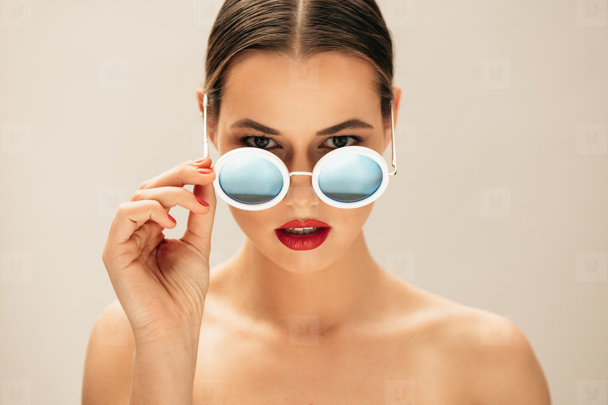 Fashion woman peeking over sunglasses