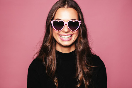 Beautiful young woman with heart shaped sunglasses