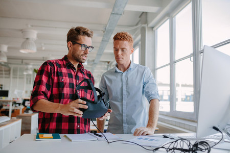Young men testing virtual reality goggles in office