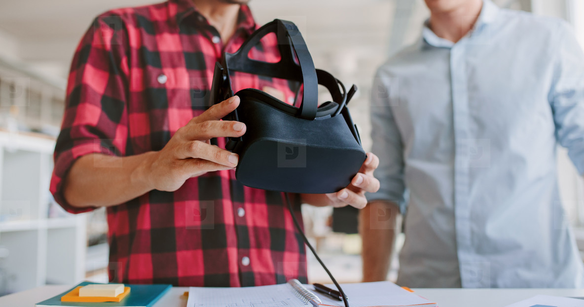 Business men working at desk holding VR glasses
