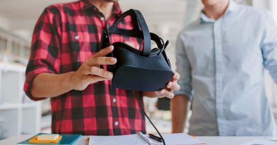 Business men working at desk holding VR glasses