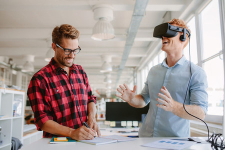 Developers testing virtual reality glasses in office