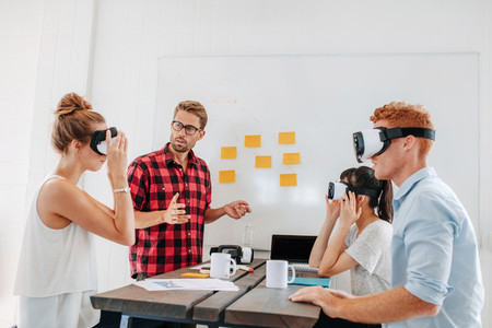 Business team testing virtual reality headset in meeting