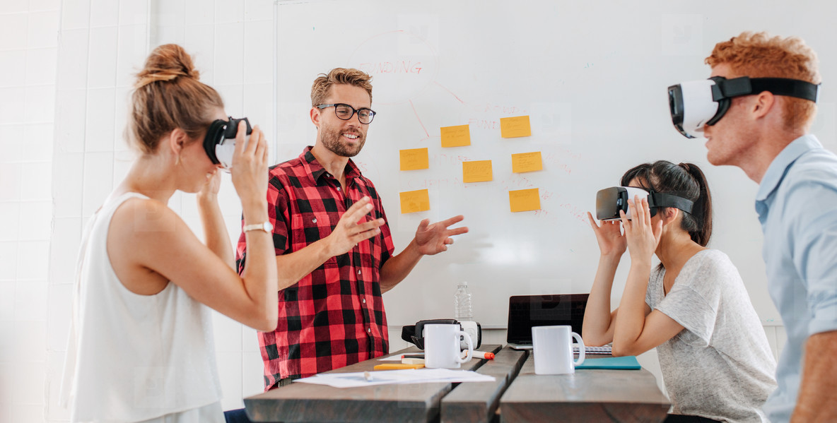 Business people using virtual reality goggles during meeting