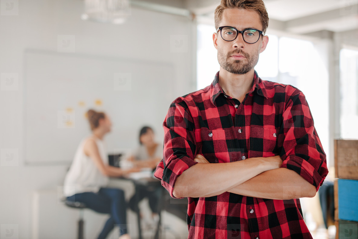 Confident young entrepreneur standing in office