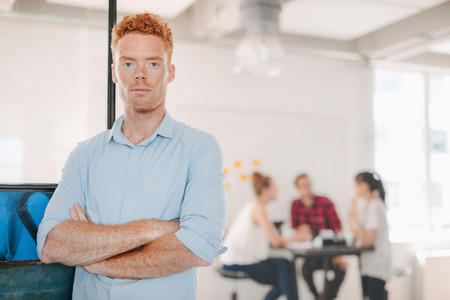 Confident young businessman standing in office