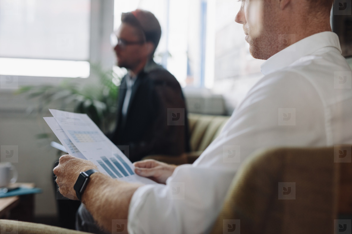 Businessman reading charts during meeting
