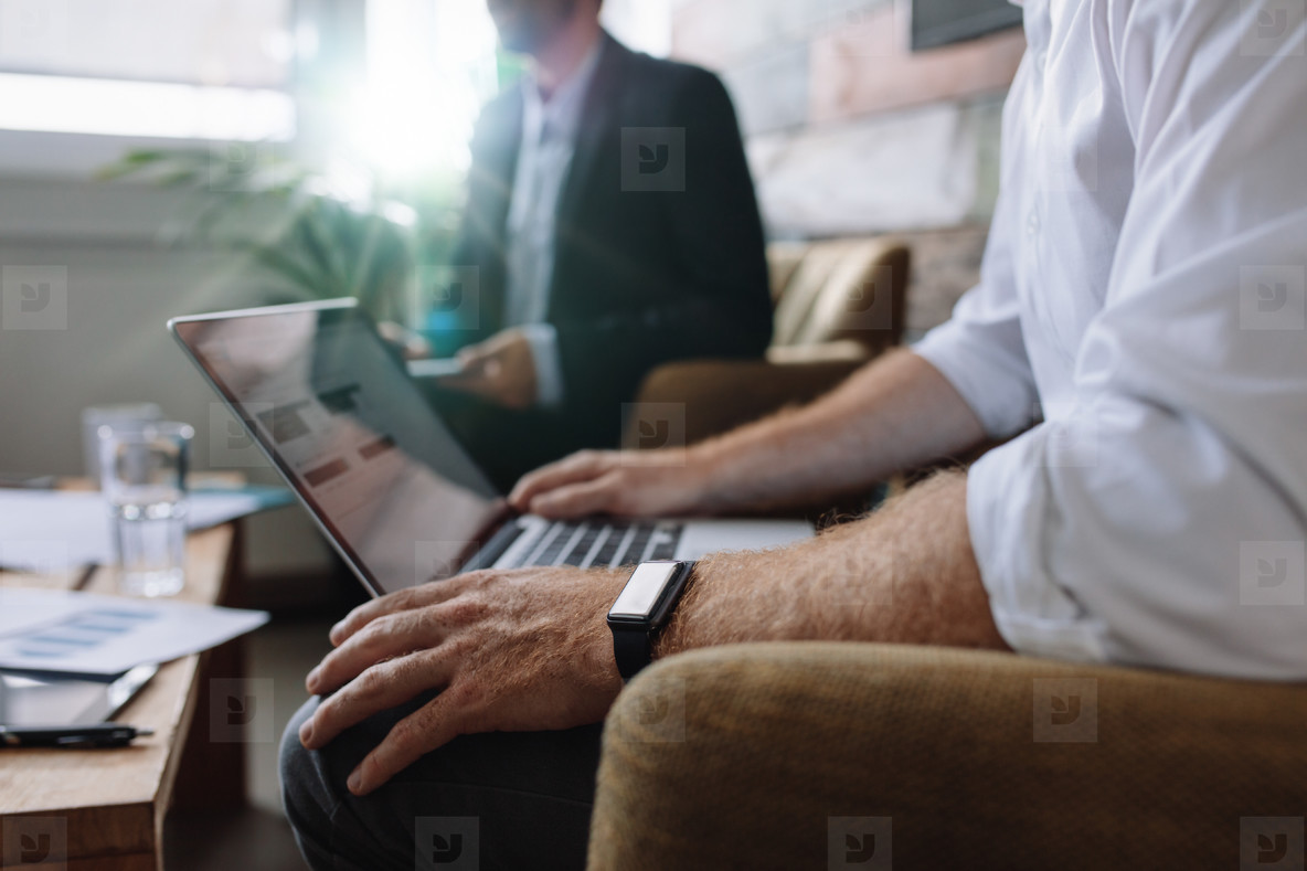 Businessman working on laptop during corporate meeting