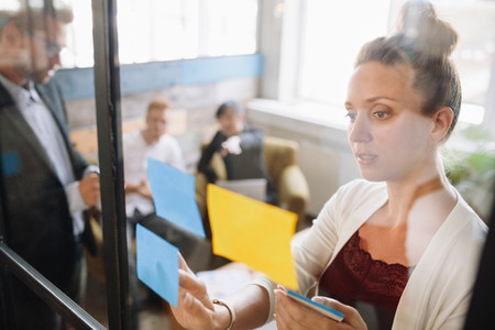 Business woman looking at adhesive notes in conference room