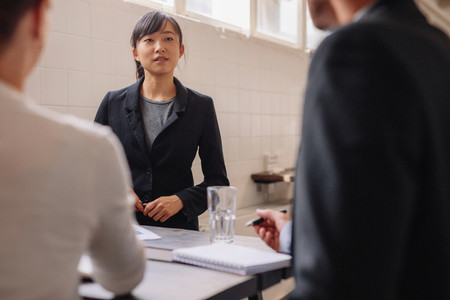 Businesswoman interacting with colleagues during presentation