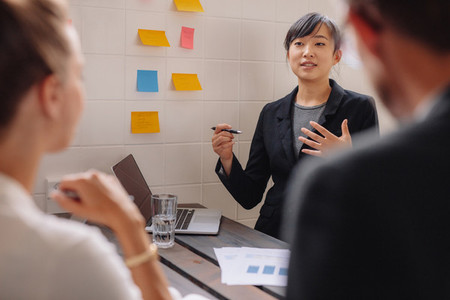 Young female executive giving presentation to colleagues
