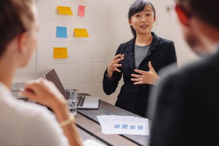 Female executive explaining new business idea to colleagues