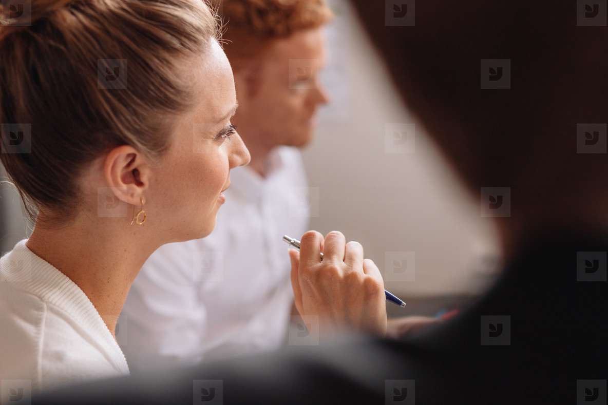Young female listening to presentation in conference room