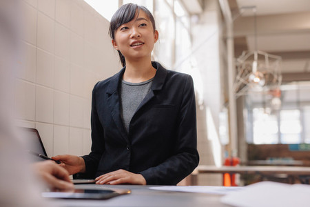 Confident asian business woman giving presentation