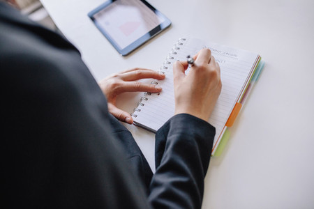 Businesswoman hands writing on notepad