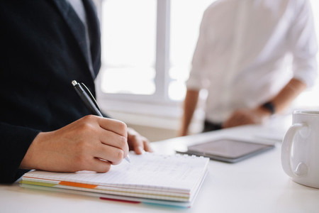 Woman taking notes with male colleague in background
