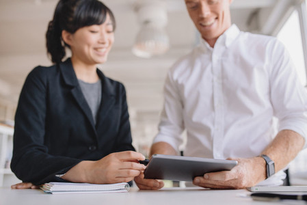 Businesspeople using digital tablet in office