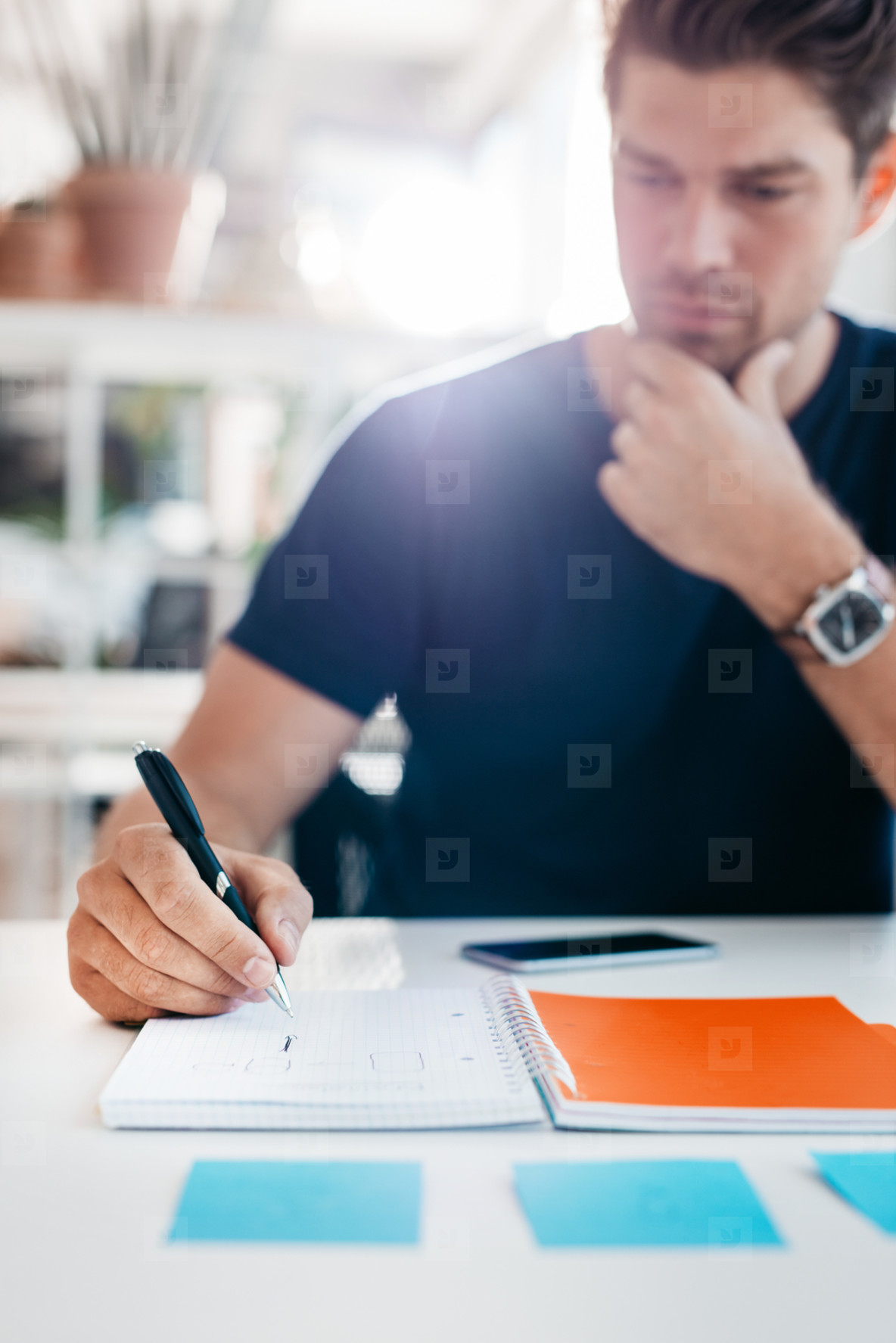 Businessman writing down important notes in office diary