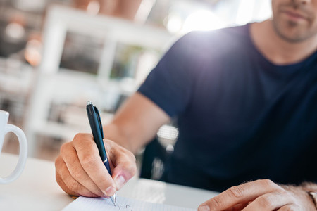 Young man hands writing in a office diary