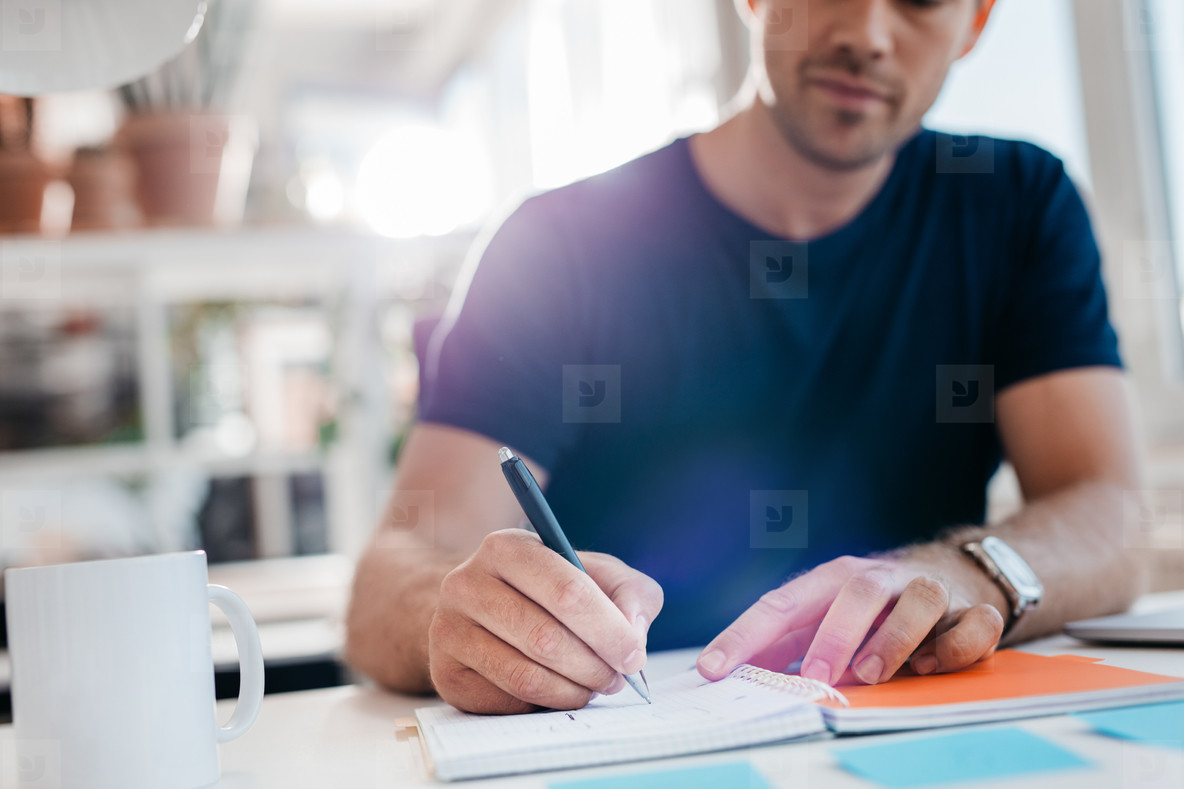 Businessman writing down important notes in diary at his desk