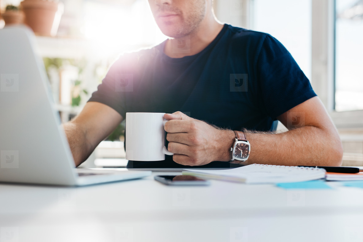 Young man with cup of coffee working on laptop