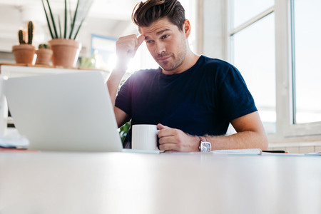 Thoughtful young man sitting at his workplace in office