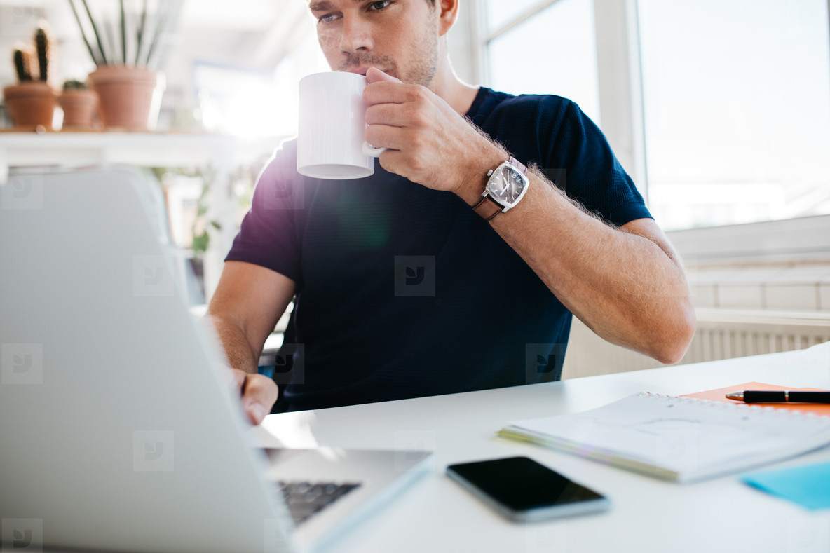Businessman drinking coffee and working on laptop