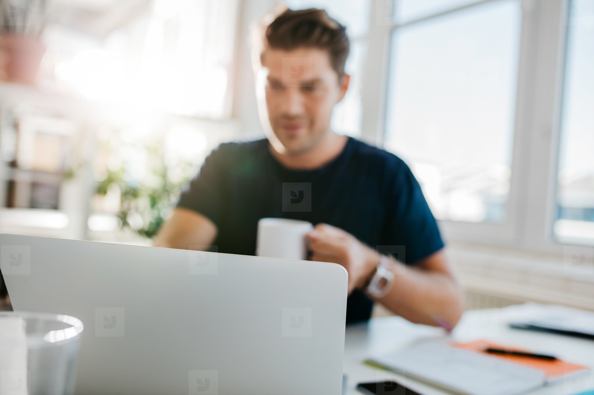 Laptop on table with man sitting by