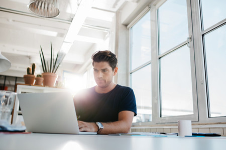 Young male executive working on laptop at his desk