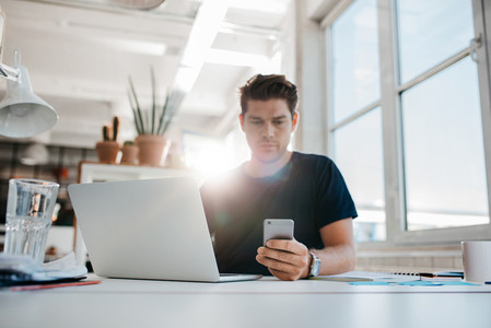 Businessman reading text message on his mobile phone