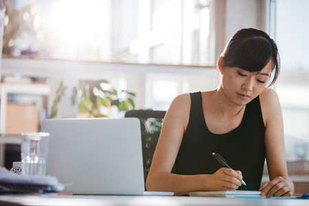 Young woman sitting at desk and writing notes