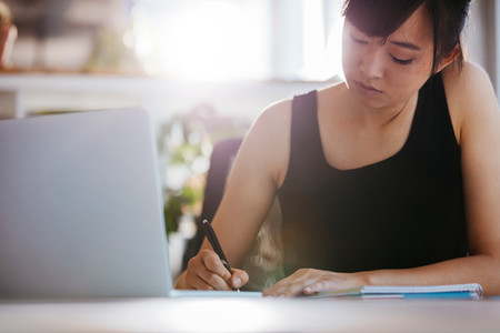 Young woman working at her desk taking notes