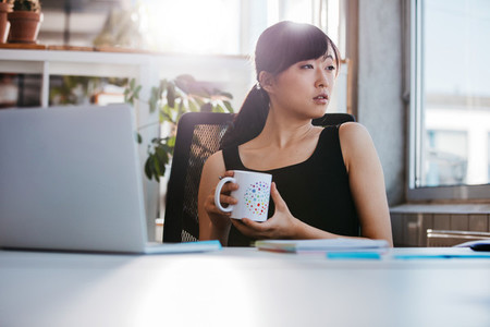 Business woman taking coffee break in office