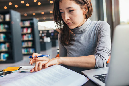 Young woman studying on a book and taking notes