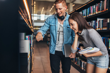 Students at college library looking for books