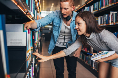Young students finding reference books in university library