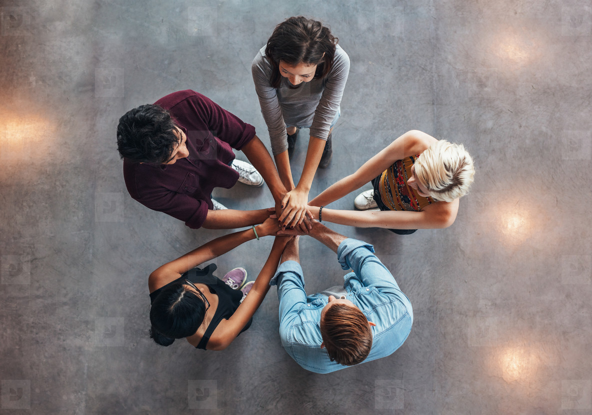 Young people making a stack of hands