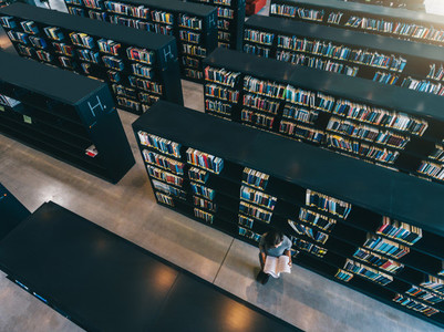 Female student at library bookshelf reading book