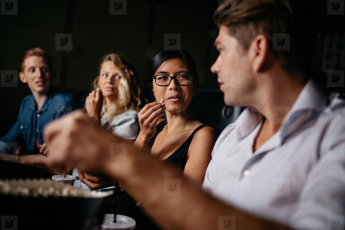 Friends sitting in multiplex movie theater