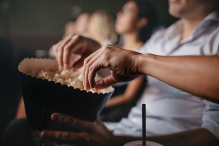 Young people eating popcorn in movie theater