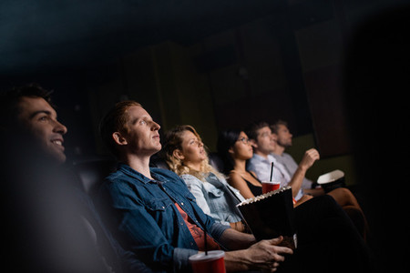 Young man with friends in cinema hall watching movie