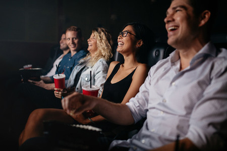 Young people in theater watching movie and smiling