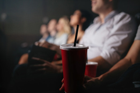 People with soft drinks in movie theater