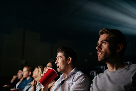 Young man watching movie with friends in cinema hall