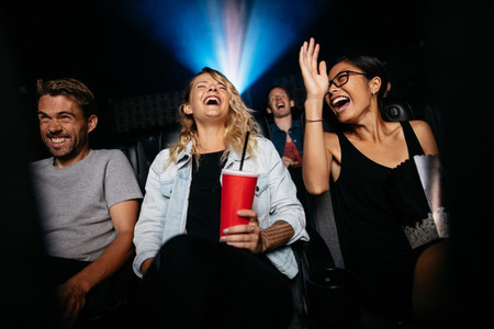 Young friends watching comedy movie on theater