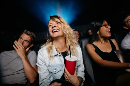 Smiling young woman watching woman in theater