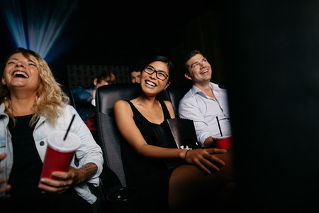 Smiling people watching comedy film in theater
