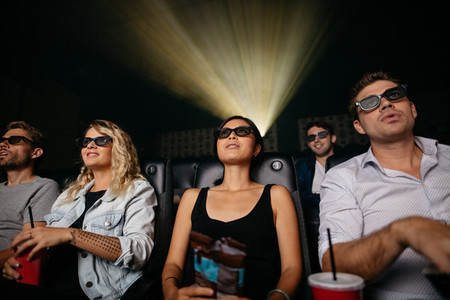Young people watching 3d movie in theater