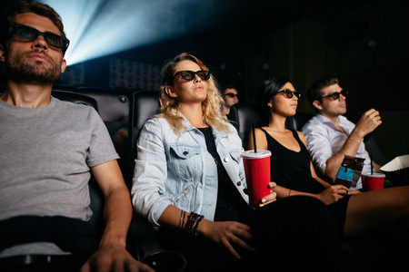 Young people with drinks watching 3d film