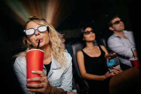 Young woman having cold drink and watching 3d movie